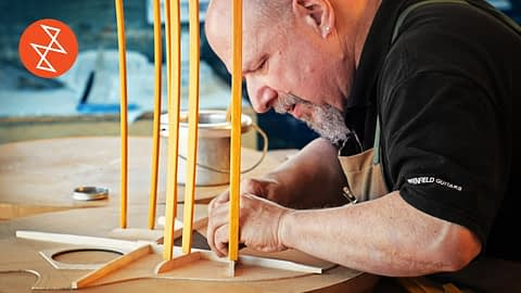 Old Man Carefully Building A Guitar